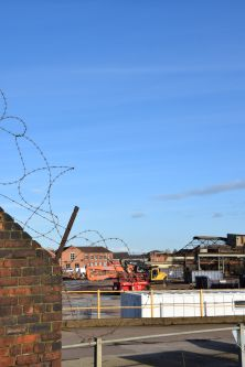 Looking through barbed wire into a once abandoned steel factory, now turned construction site